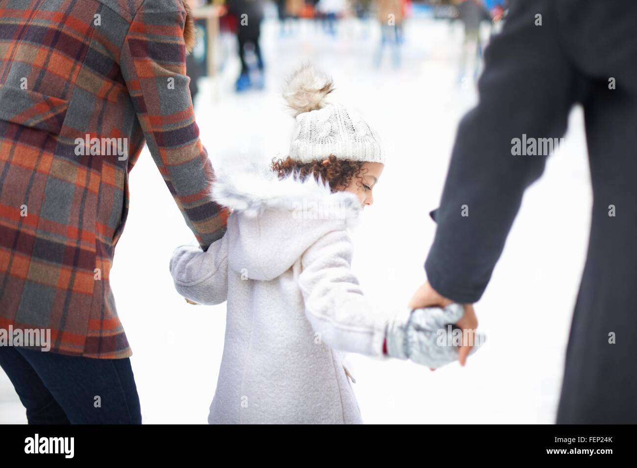 Rear view of girl ice skating with parents, holding hands - Stock Image