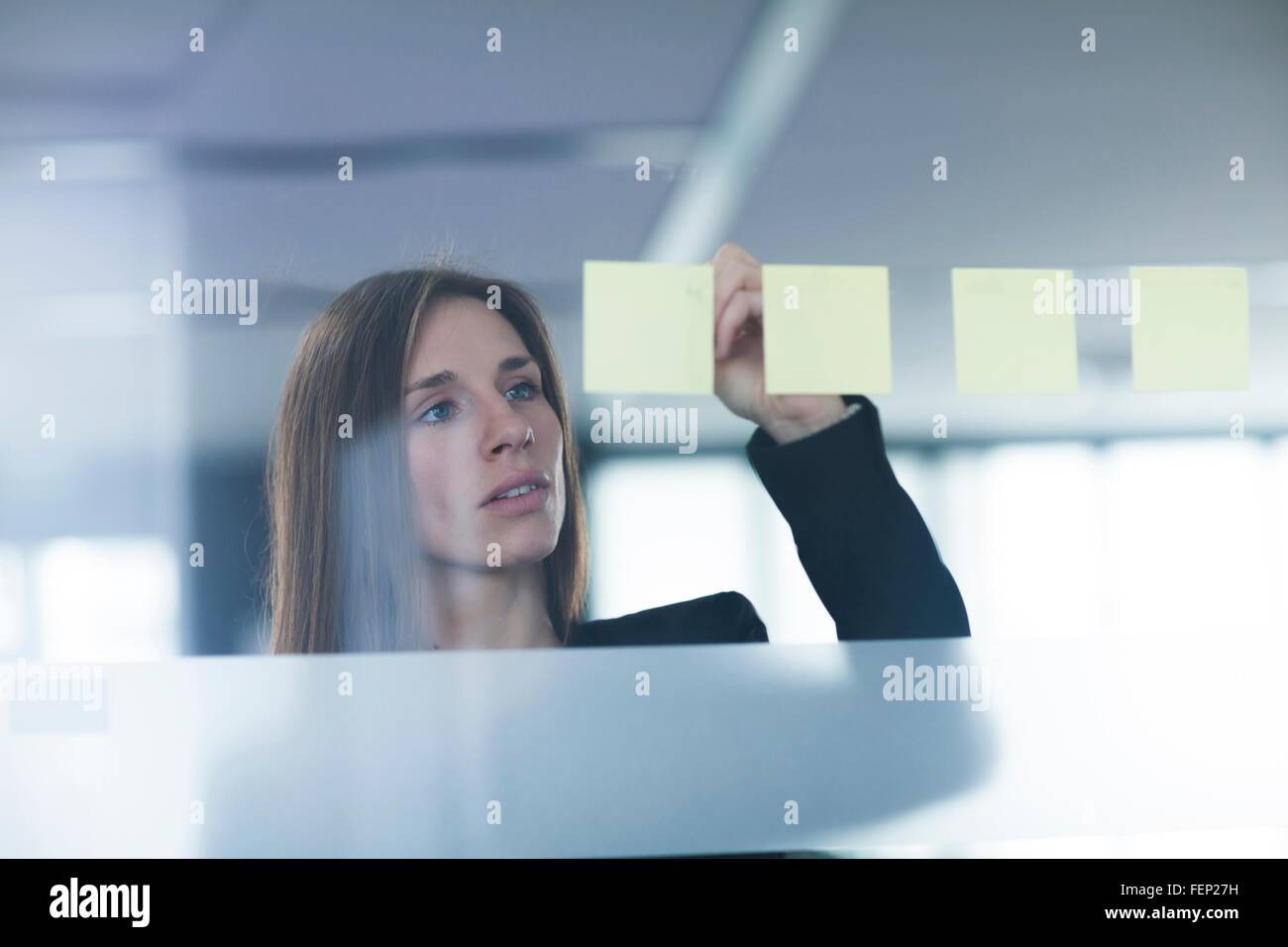 View through window of young woman writing on post it note stuck to glass Stock Photo