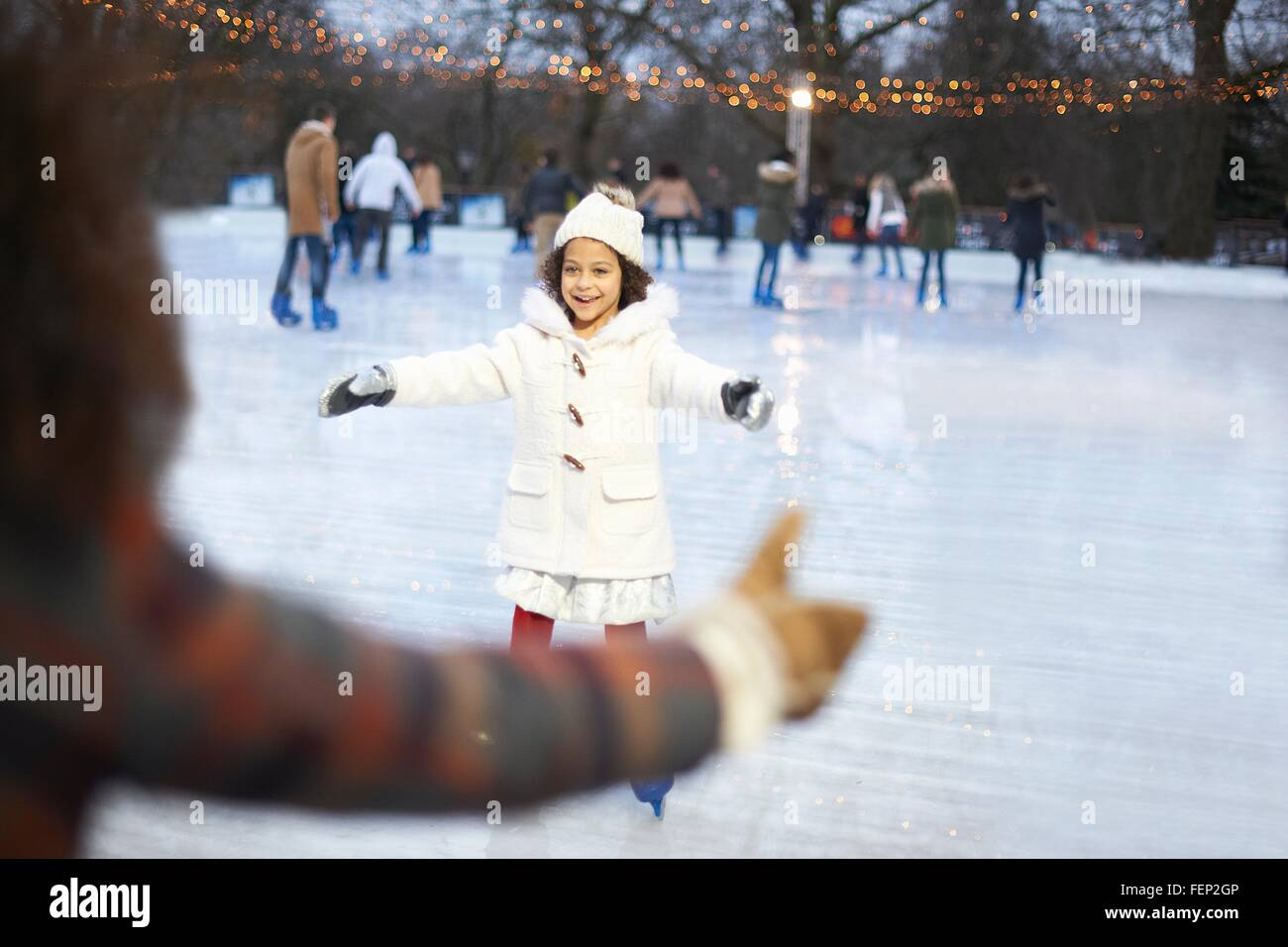Girl on ice rink, arms open skating to mother smiling - Stock Image