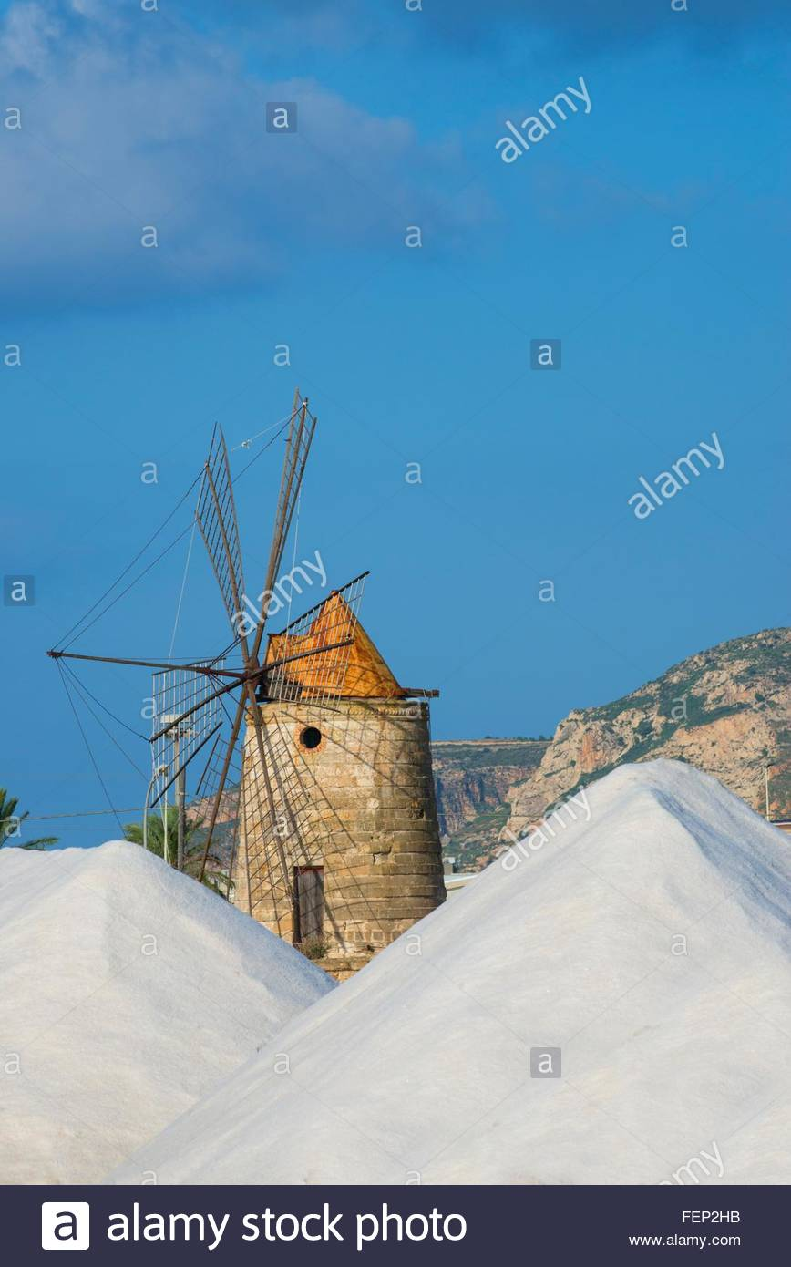 Salt stacks and traditional windmill, Trapani, Sicily, Italy - Stock Image