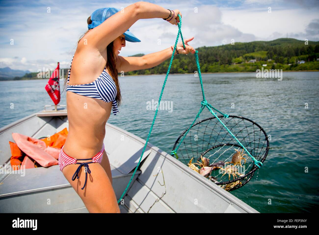 Young woman hauling in crab trap on fishing boat, Nehalem Bay, Oregon, USA Stock Photo