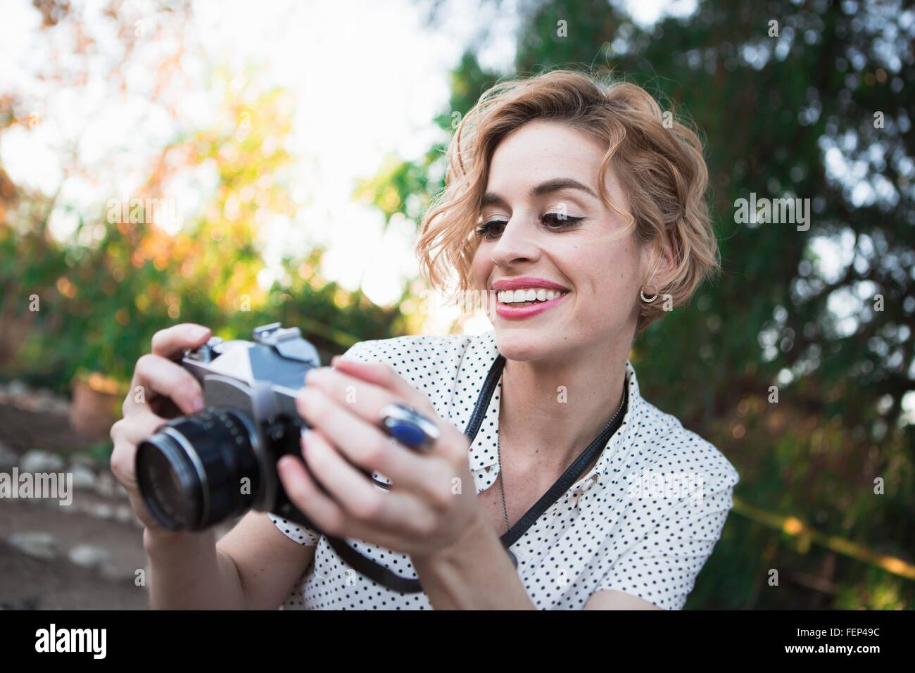 Mid adult woman looking at back of camera, outdoors, smiling - Stock Image