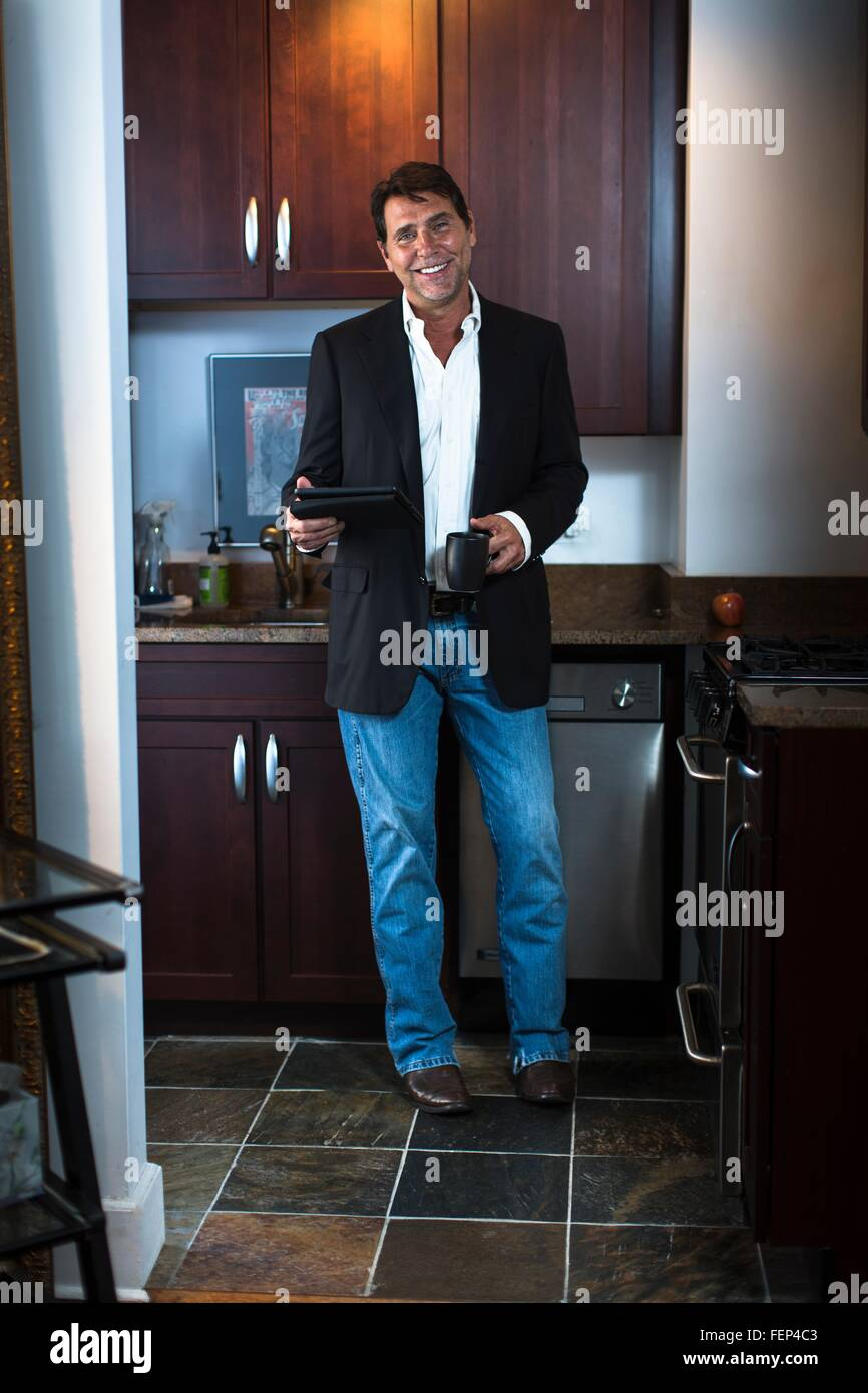 Mature man wearing suit jacket and jeans in kitchen, holding digital tablet and coffee mug, looking at camera smiling - Stock Image