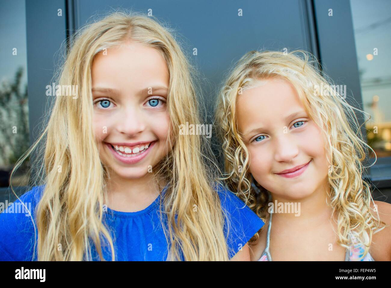 Portrait of blond haired and blue eyed sisters at sidewalk cafe - Stock Image