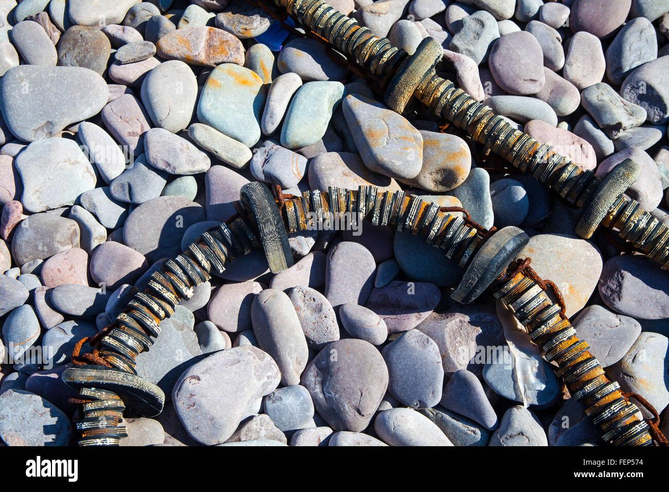 Stone pebbles on a beach in bright sun light - Stock Image