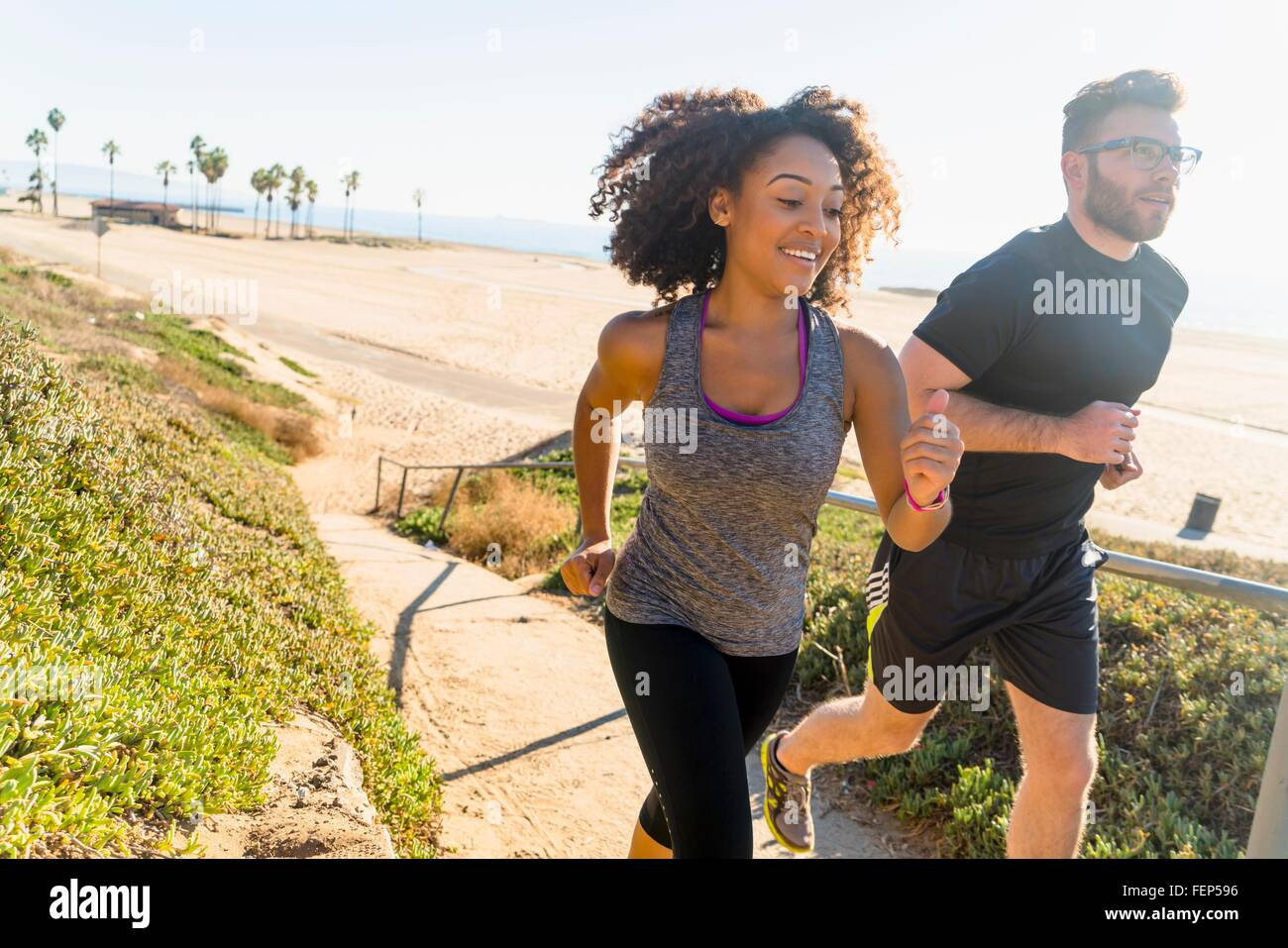 Couple running along pathway by beach - Stock Image