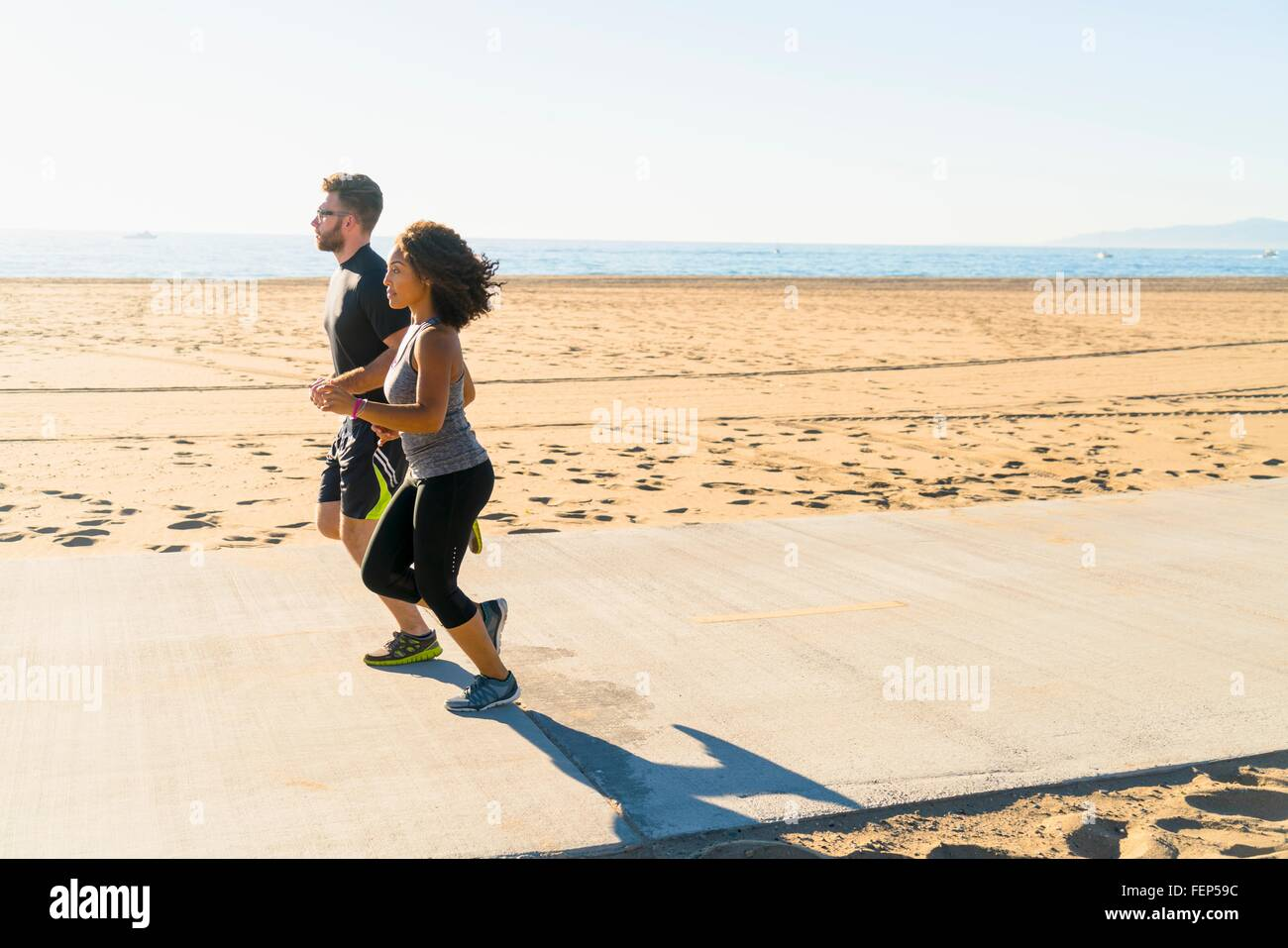 Couple running on pathway at beach - Stock Image