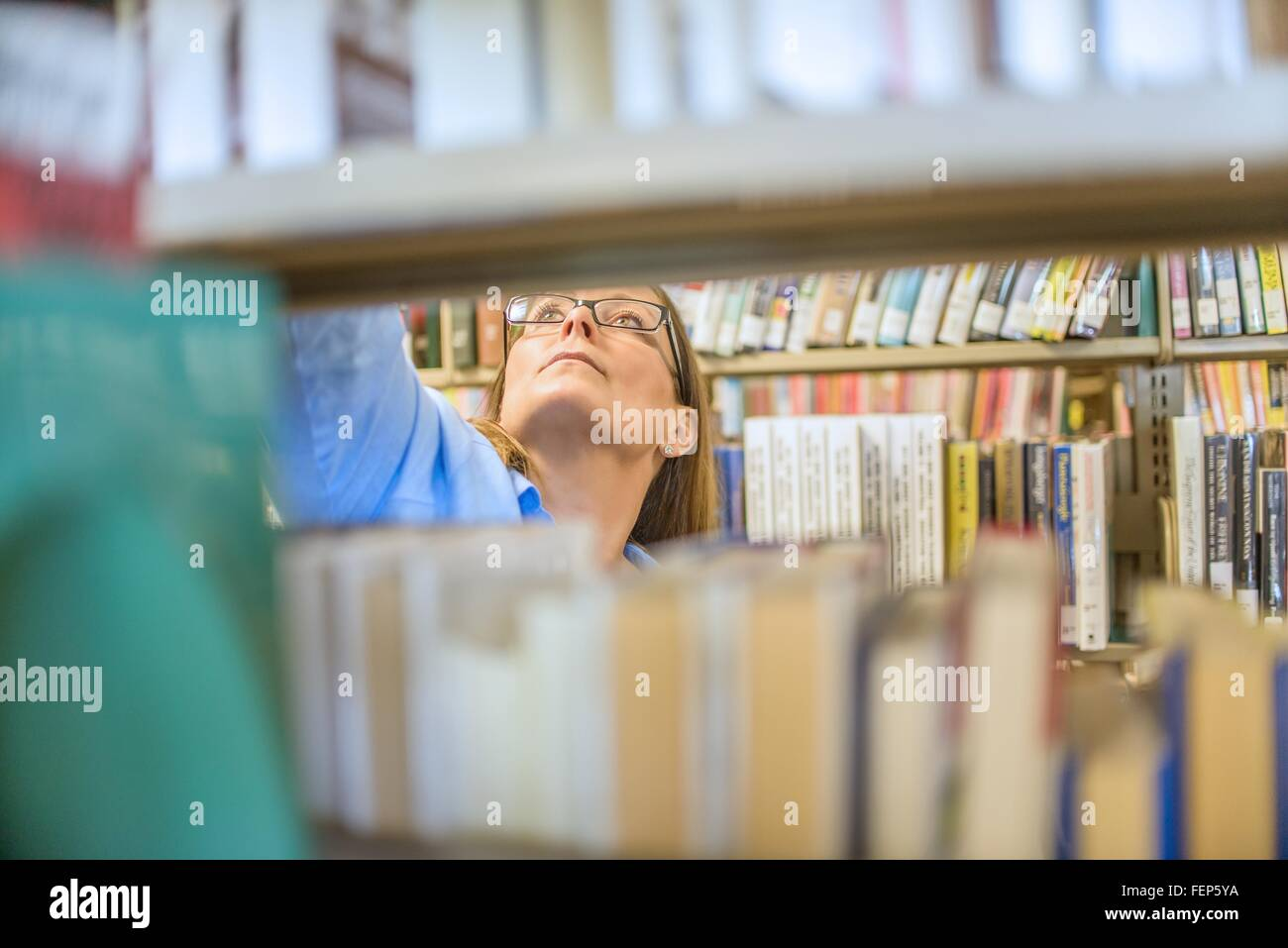 Mature woman behind book shelves in library - Stock Image