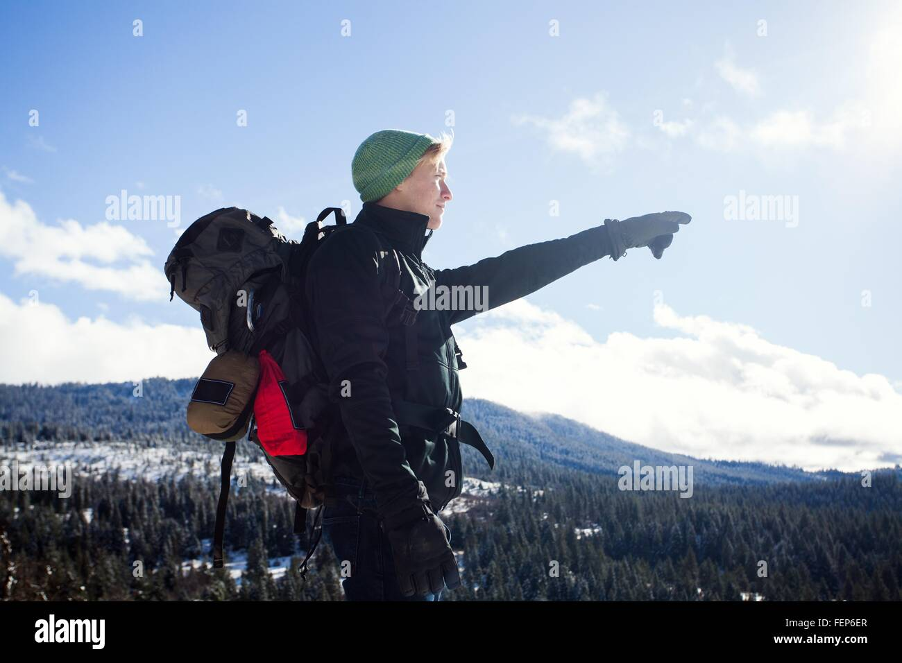 Young male hiker pointing out to mountain forests, Ashland, Oregon, USA - Stock Image