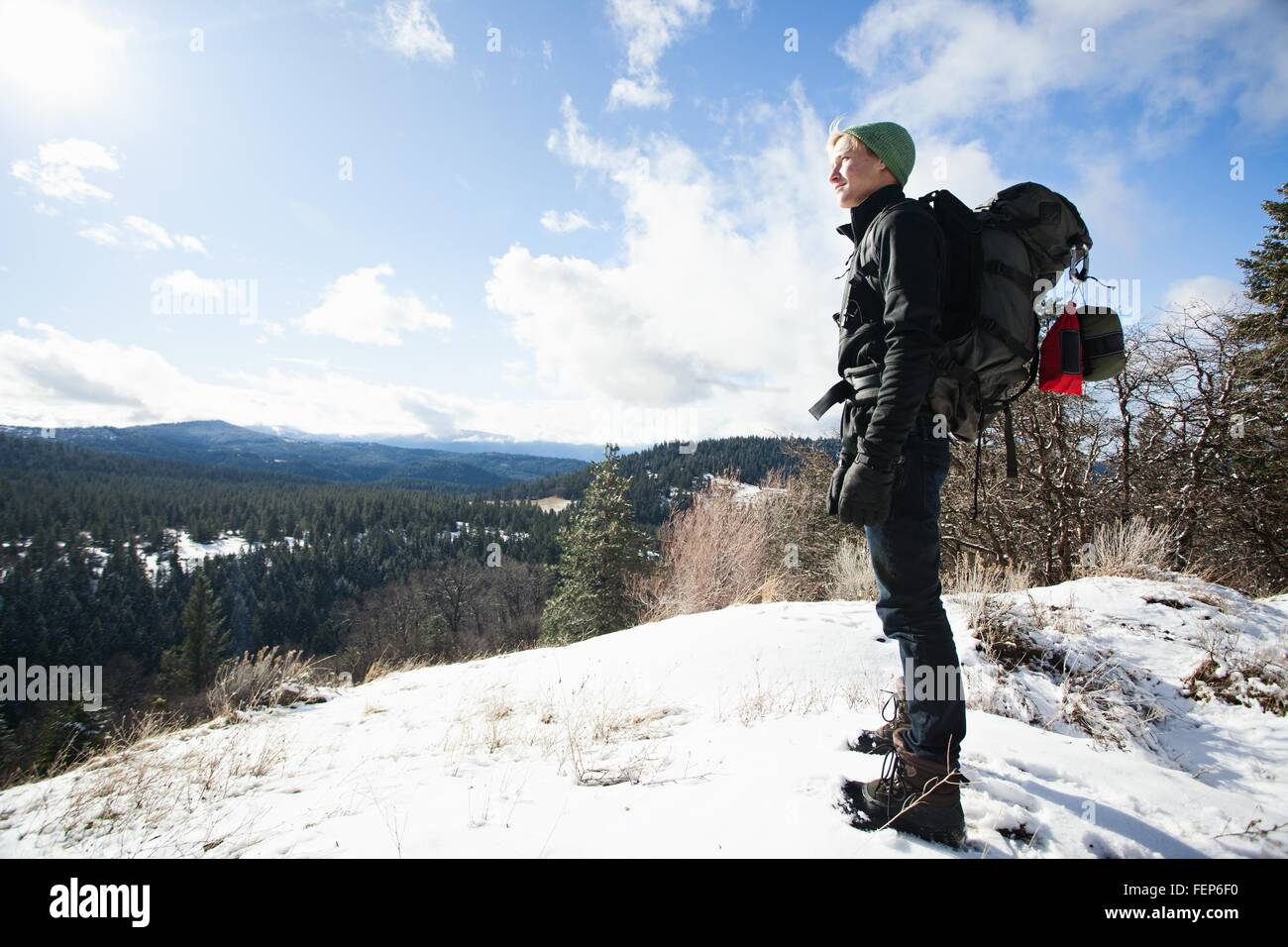 Young male hiker looking out from snow covered landscape, Ashland, Oregon, USA - Stock Image