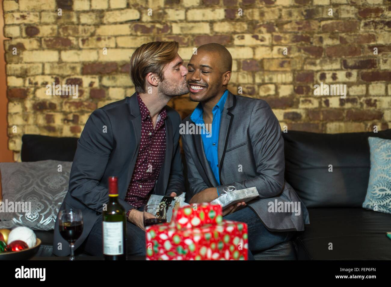 Male couple sitting on sofa exchanging Christmas gifts young man kissing partner on cheek  sc 1 st  Alamy & Male couple sitting on sofa exchanging Christmas gifts young man ...