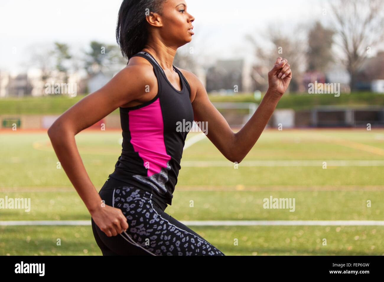 Young woman running on race track - Stock Image