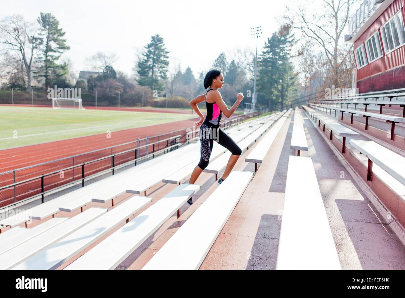 Young woman running up steps at sports track - Stock Image