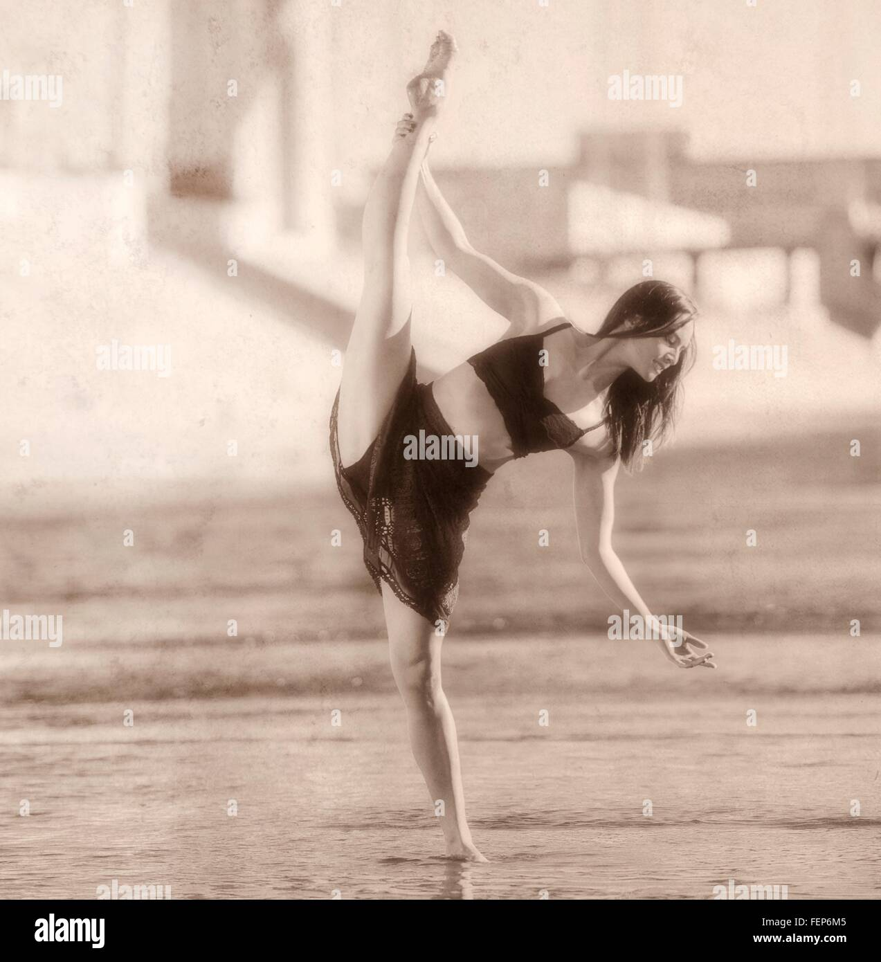 Young woman leg raised, balancing on one leg, b&w, Los Angeles, California, USA - Stock Image