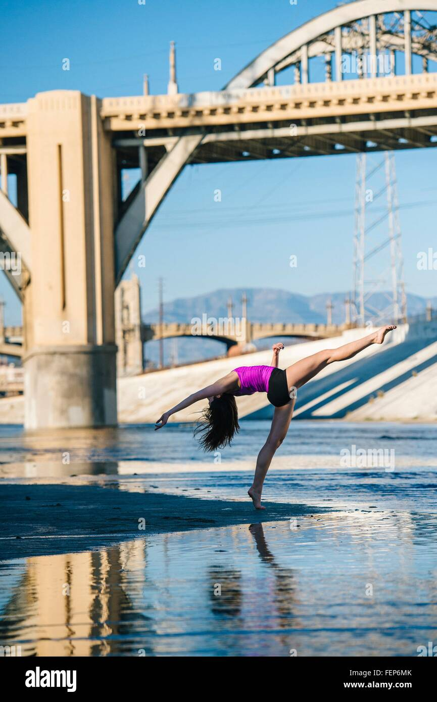 Side view of dancer, leg raised, bending over backwards in front of bridge, Los Angeles, California, USA - Stock Image