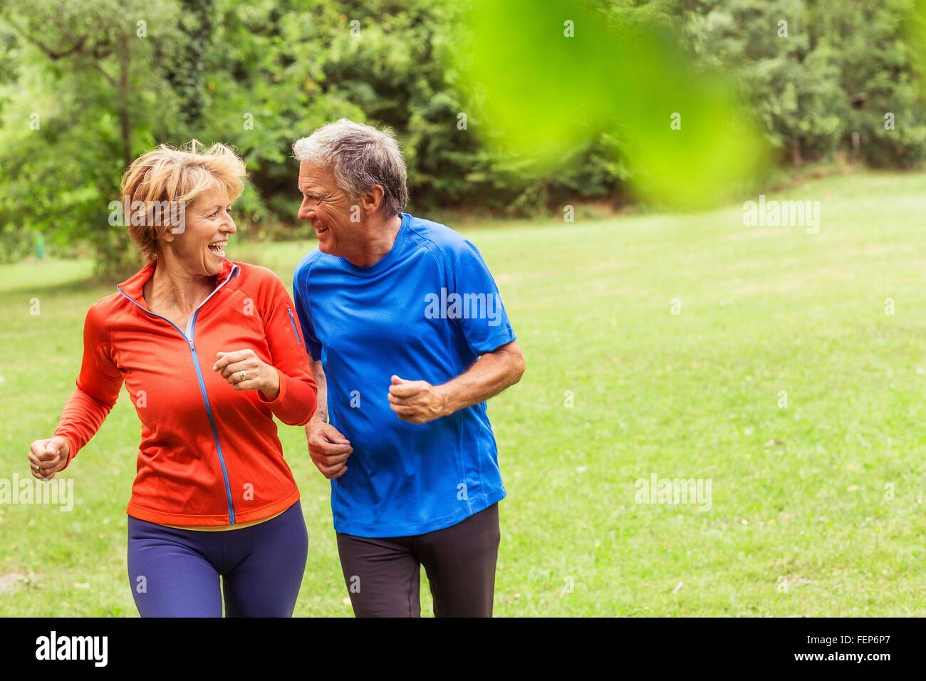 Couple running together outdoors, laughing - Stock Image