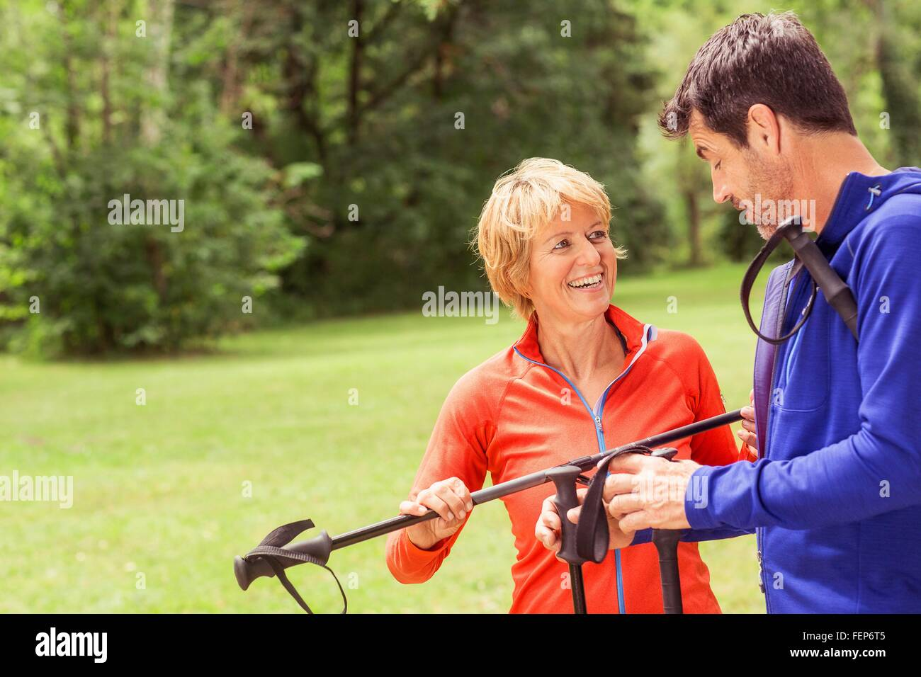Couple outdoors with walking poles - Stock Image