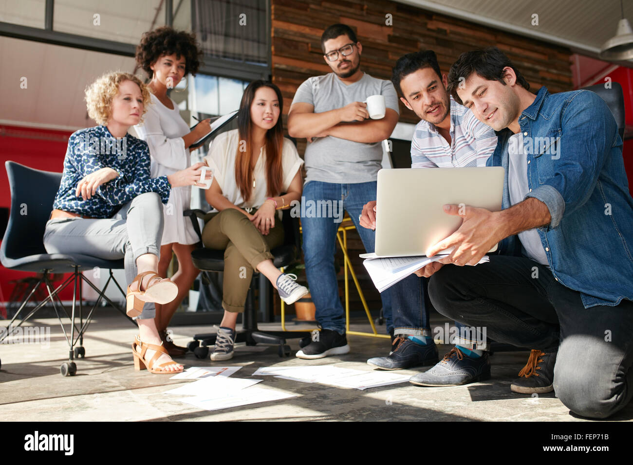 Startup team working and planning in the meeting. Group of young men and women looking at laptop at office. - Stock Image