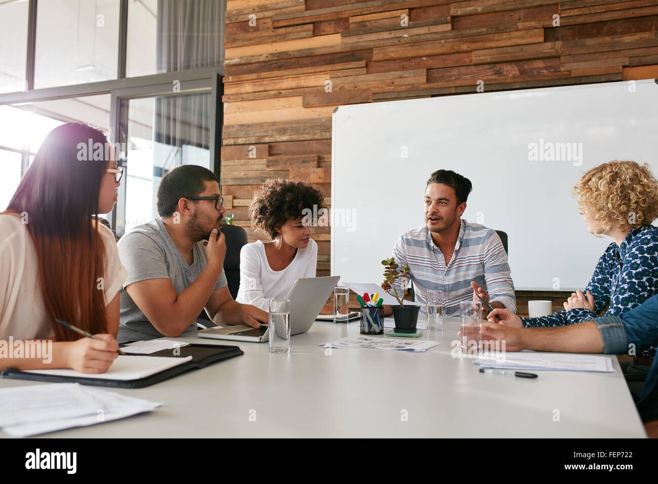 Shot of a group of young business professionals having a meeting in boardroom. Office workers discussing new business - Stock Image