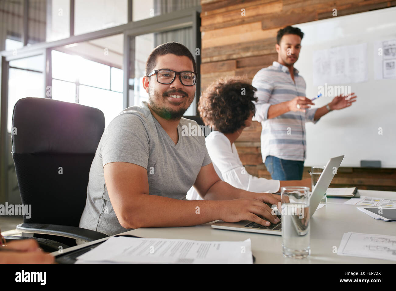 Smiling young man sitting at a business meeting with colleagues - Stock Image