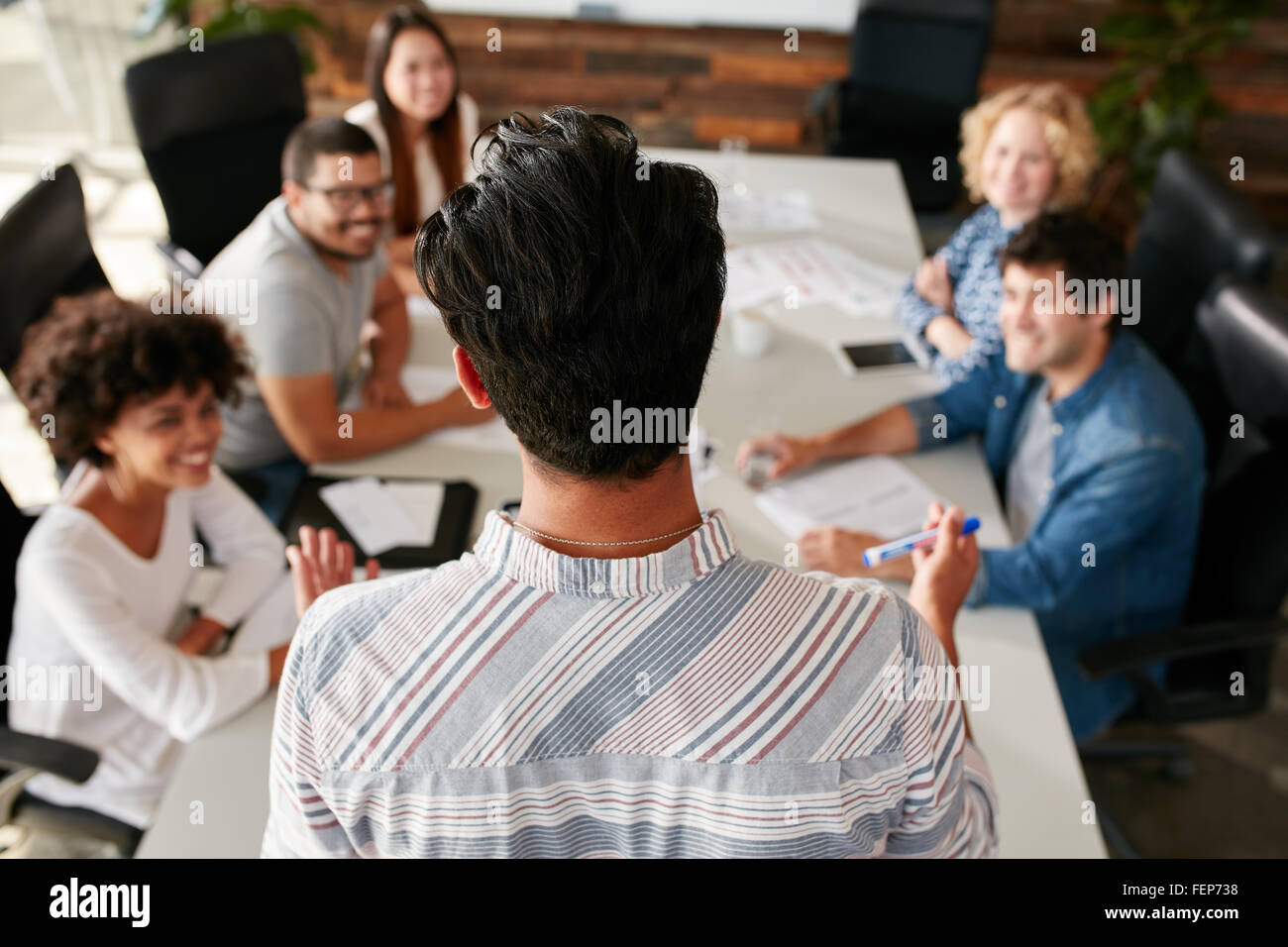 Rear view portrait of man explaining business ideas to colleagues during a meeting in conference room.  Young people - Stock Image