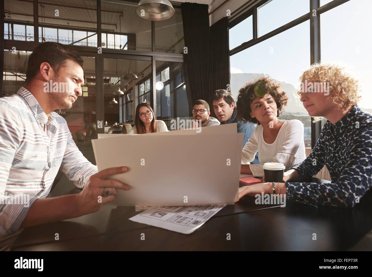 Happy and successful team of colleagues sitting together to work out business plans - Stock Image