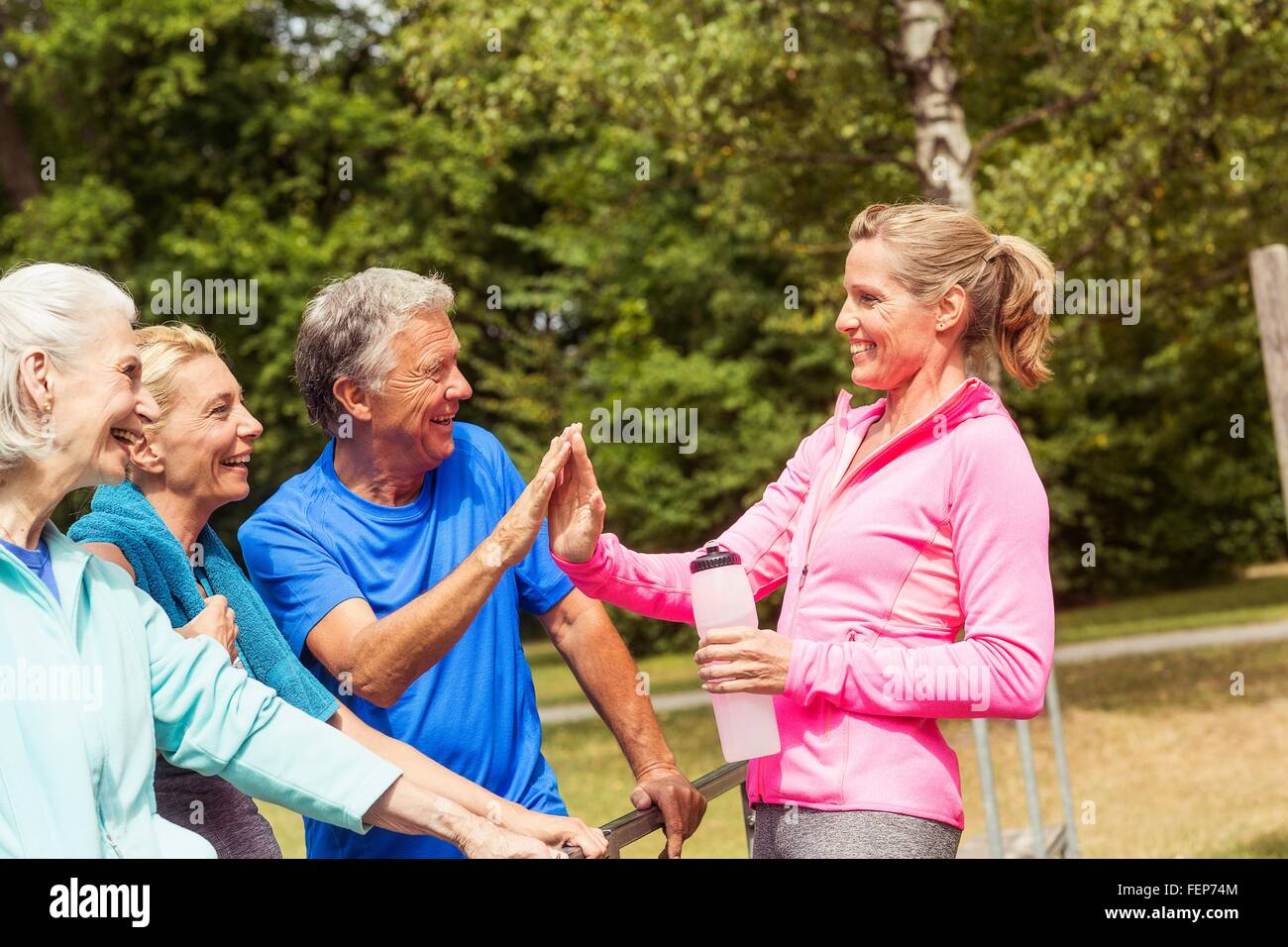 Group of adults taking a break from exercise, outdoors, smiling - Stock Image