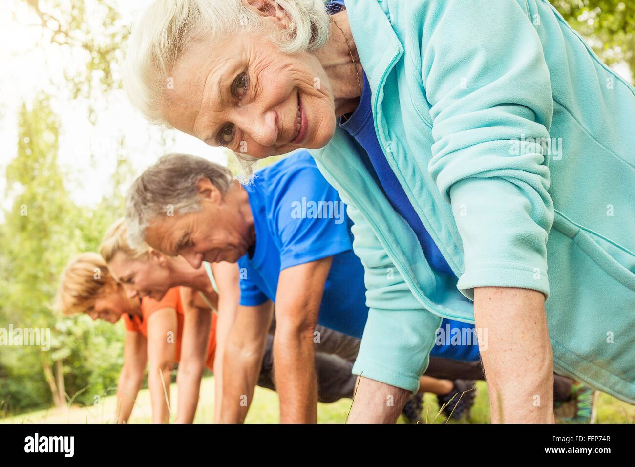 Group of adults exercising, doing push ups, outdoors - Stock Image