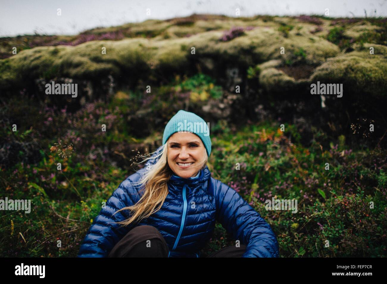 Front view of mid adult woman crouched in front of mound wearing knit hat looking at camera smiling, Iceland - Stock Image