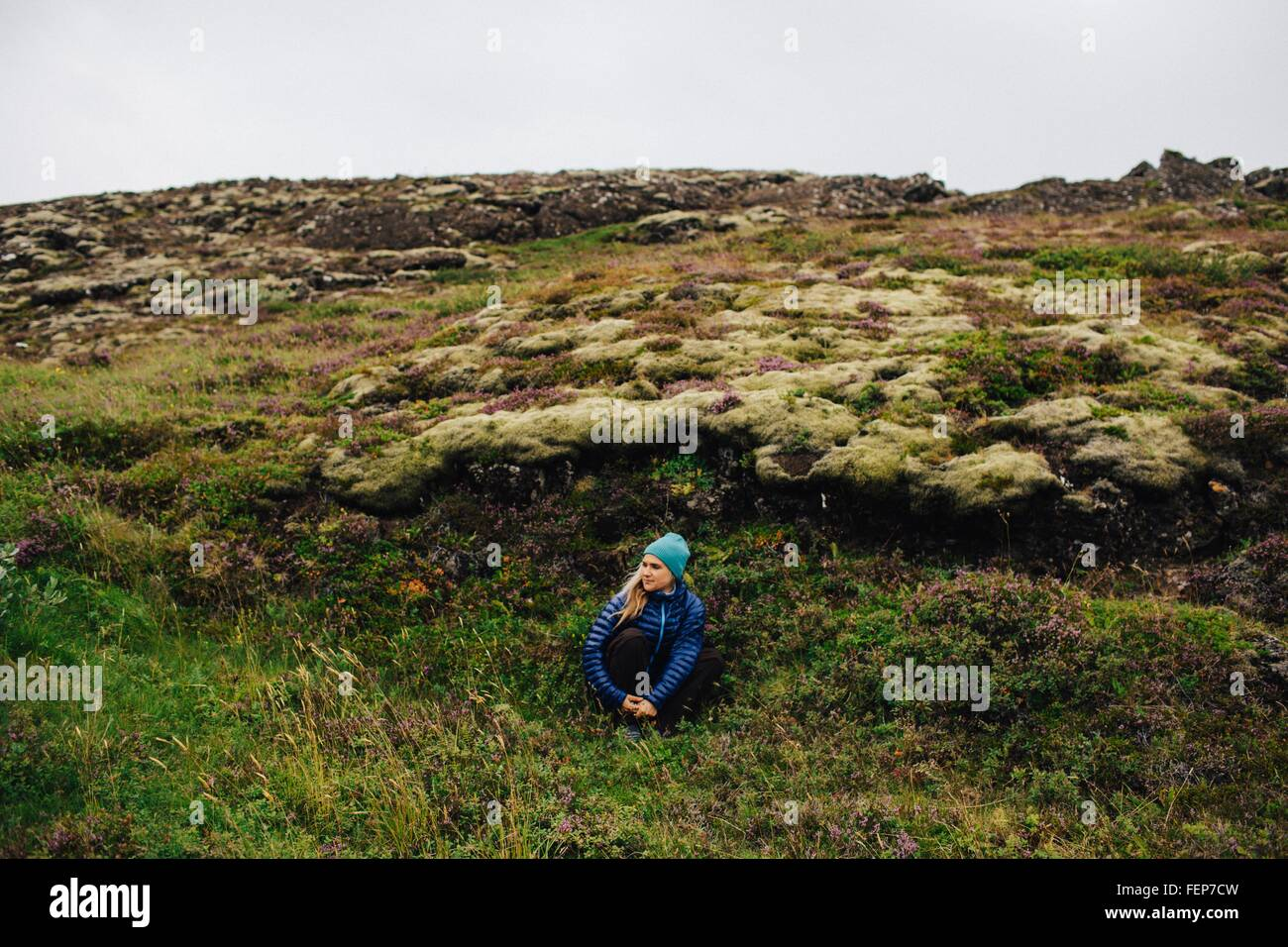 Mid adult woman crouched in front of mound wearing knit hat looking away, Iceland Stock Photo