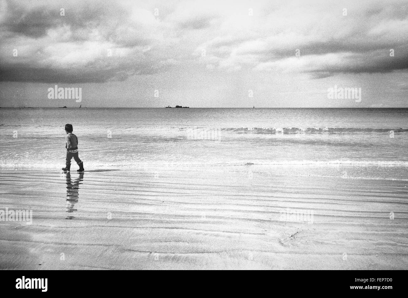 Rear View Of Boy Walking On Shore At Beach Against Sky - Stock Image