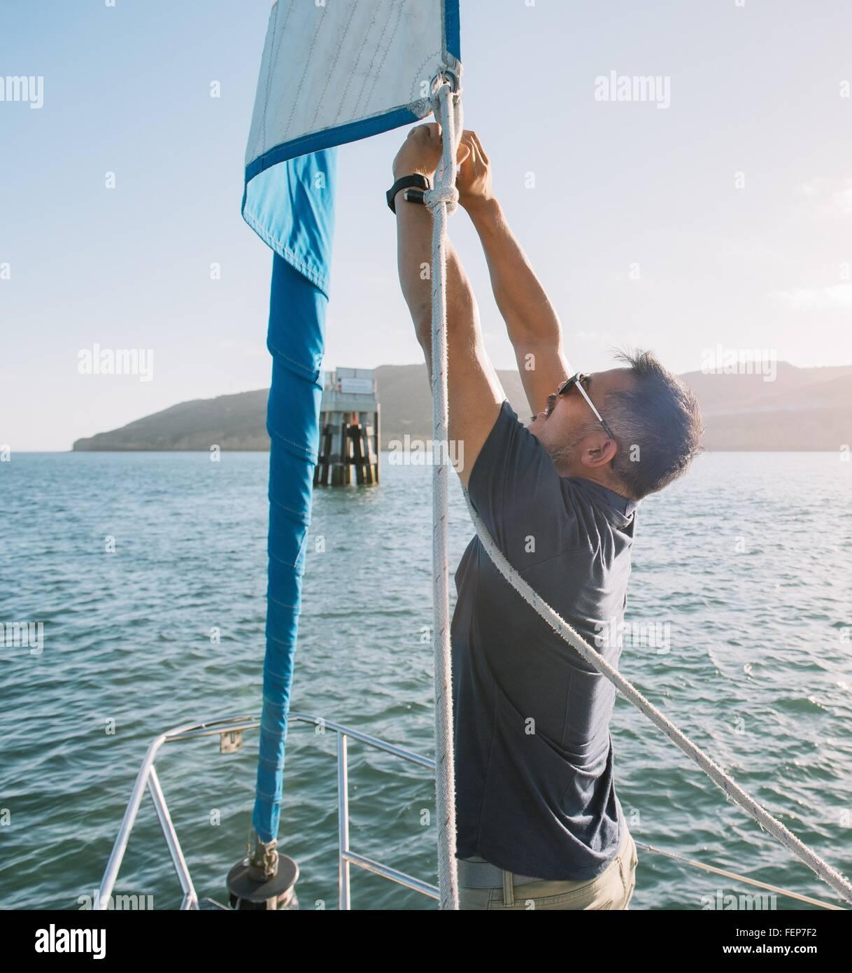 Man tying up mainsail on sailboat, San Diego Bay, California, USA - Stock Image