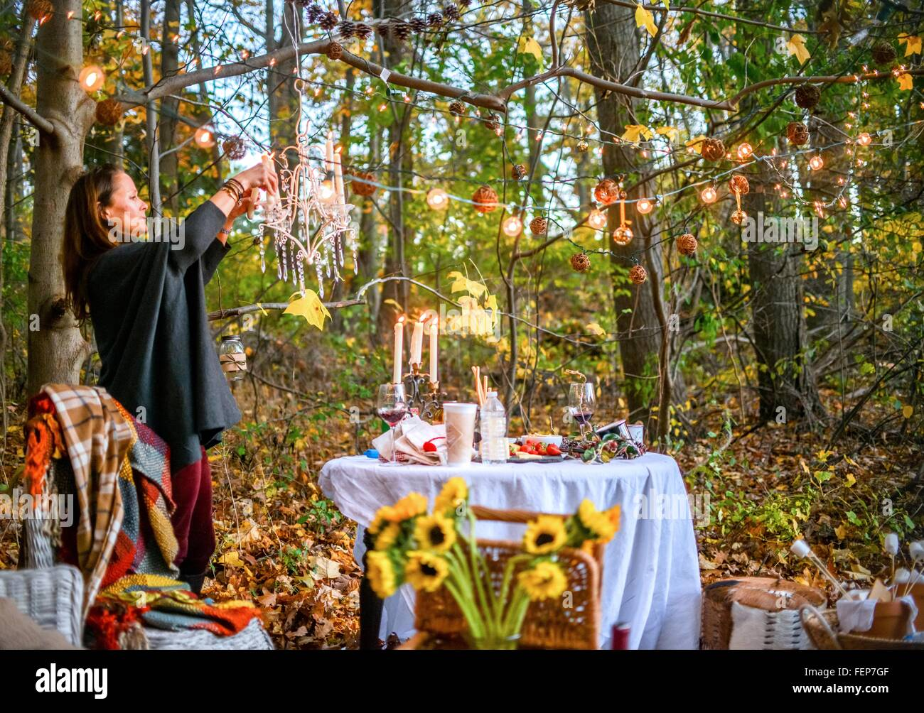Mature woman hanging decorative lights in woods Stock Photo
