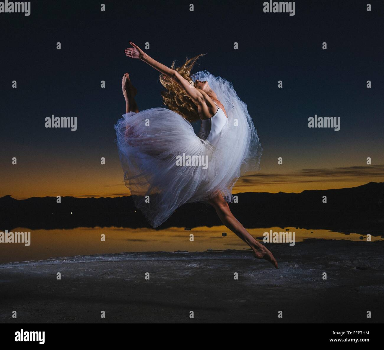 Young female ballet dancer leaping over Bonneville Salt Flats at dusk, Utah, USA - Stock Image