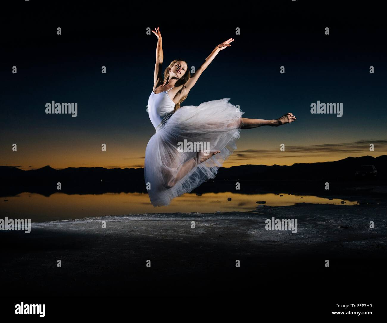 Young female ballet dancer leaping over Bonneville Salt Flats at sunset, Utah, USA - Stock Image