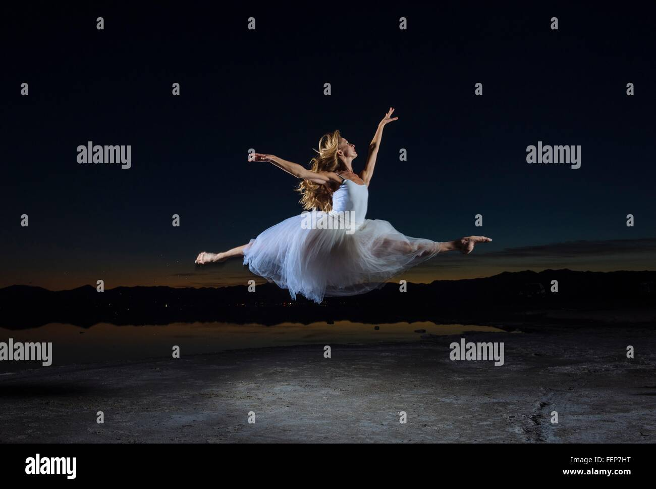 Young female ballet dancer leaping over Bonneville Salt Flats at night, Utah, USA - Stock Image