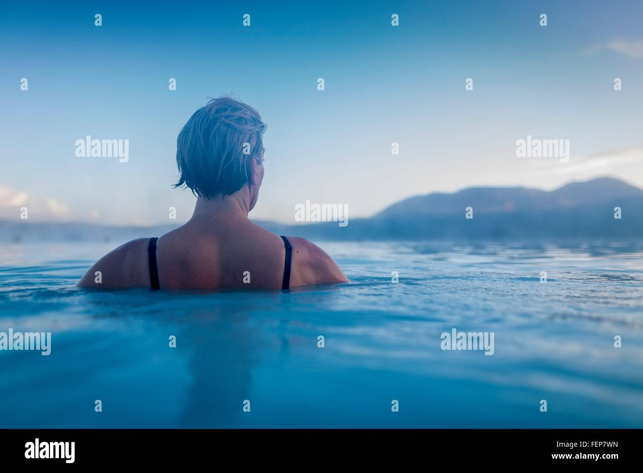 Backview of woman in lagoon waters - Stock Image