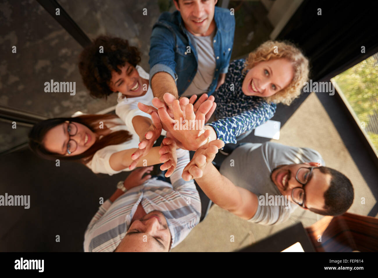 Top view of successful team of professionals high fiving and looking at camera smiling. Men and women making a pile - Stock Image