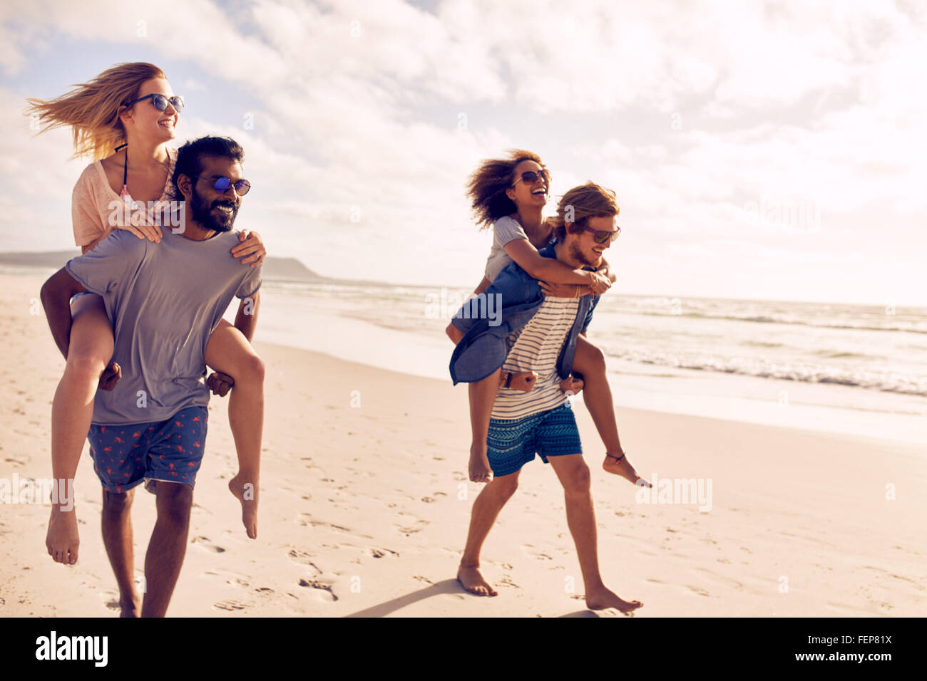 Two beautiful young couples walking by the beach, with men carrying their women on their back. Couples piggybacking - Stock Image
