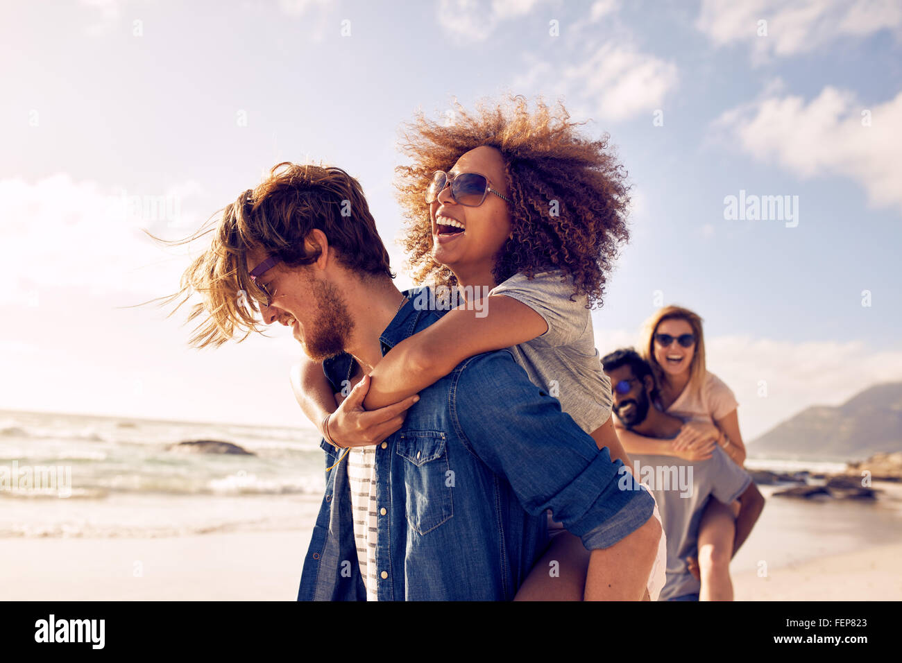 Group of friends walking along the beach, with men giving piggyback ride to girlfriends. Happy young friends enjoying - Stock Image