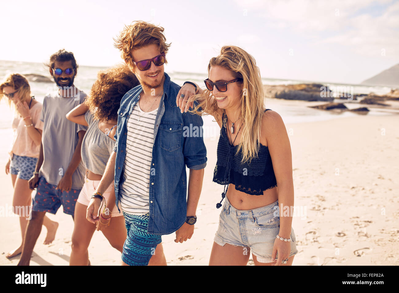 Diverse group of young friends having a walk on the beach. Young people looking happy on vacation. Young men and - Stock Image