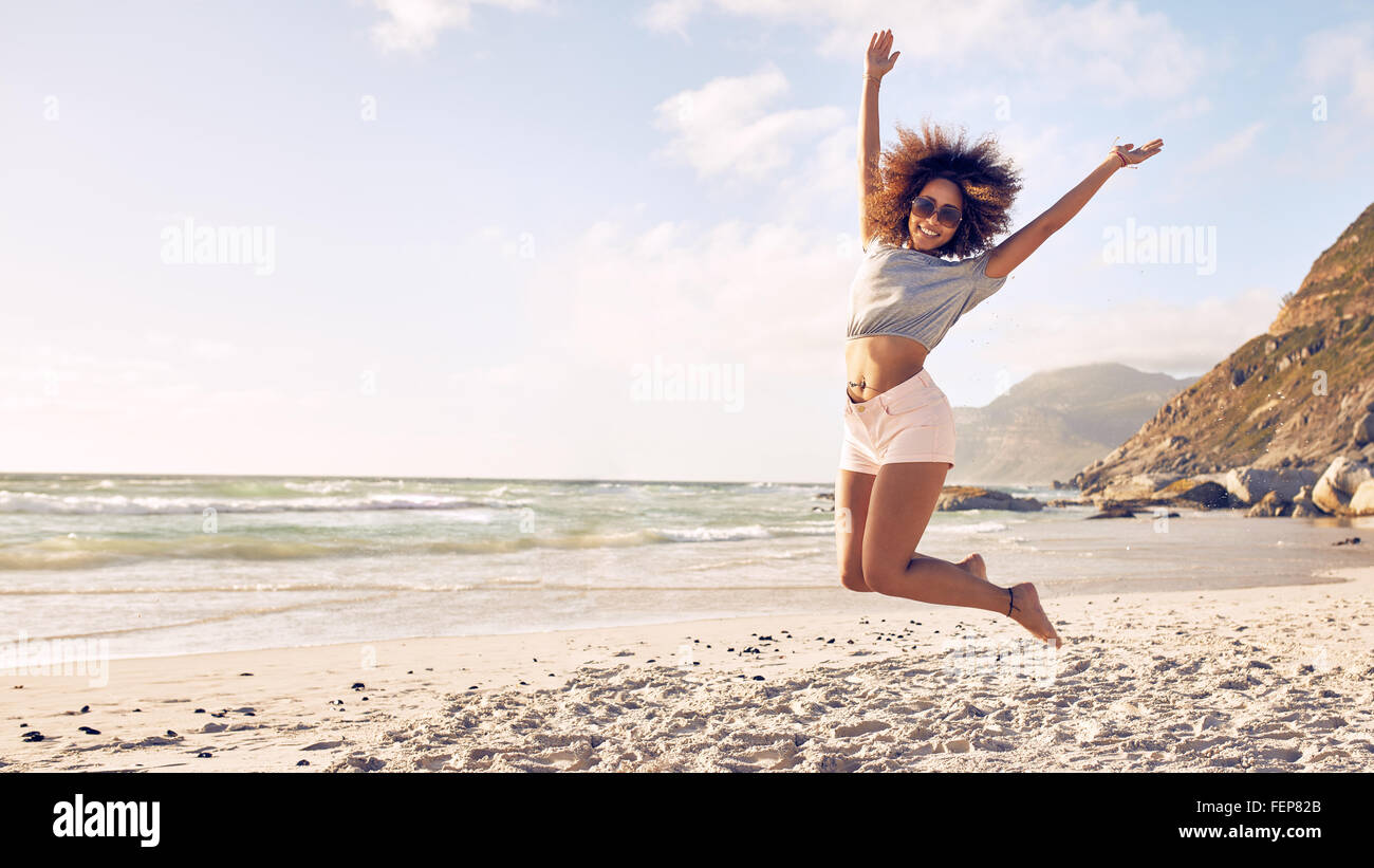 Portrait of beautiful young woman jumping in air at the beach. African female enjoying a summer day at the sea shore. - Stock Image