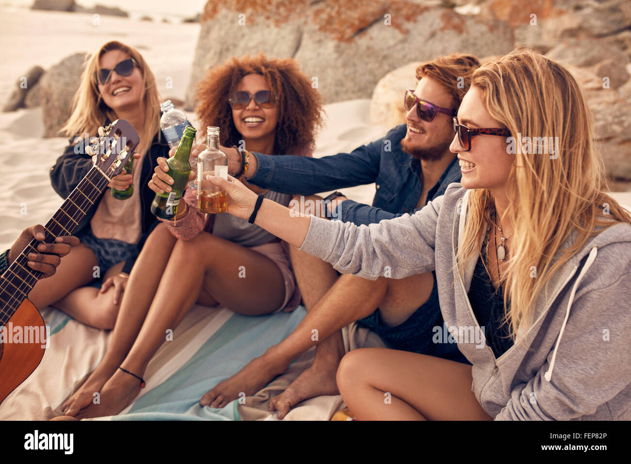 Young people sitting together at beach and having a party. Group of friends cheers with beers at the beach. - Stock Image