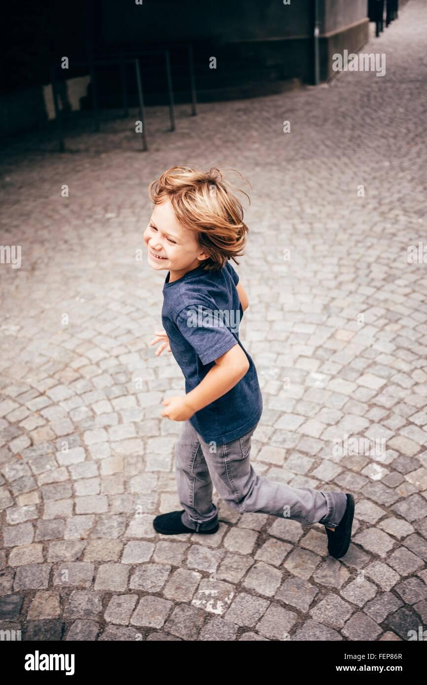 High angle side view of boy running on cobblestone smiling, Bludenz, Vorarlberg, Austria - Stock Image