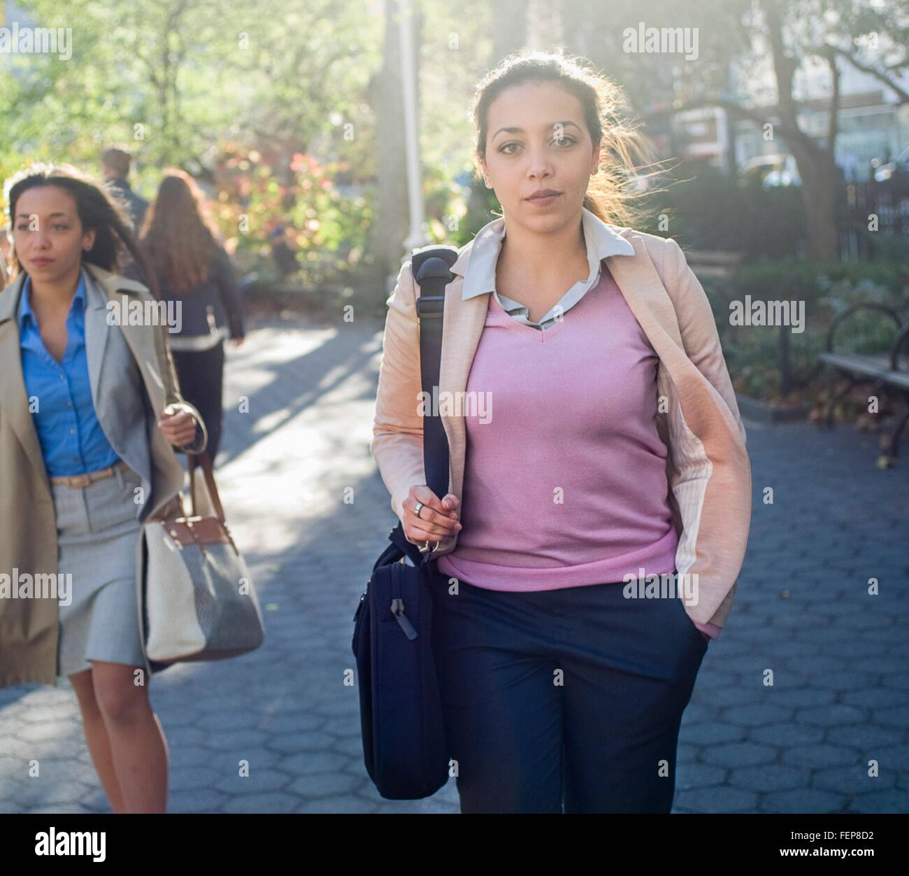 Young woman walking through city park - Stock Image