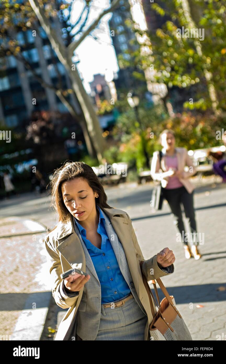 Young woman reading smartphone whilst walking through city park - Stock Image
