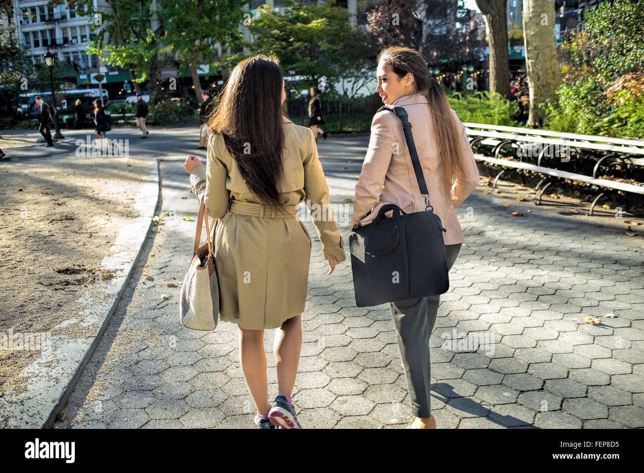 Rear view of young female twins walking through city park Stock Photo