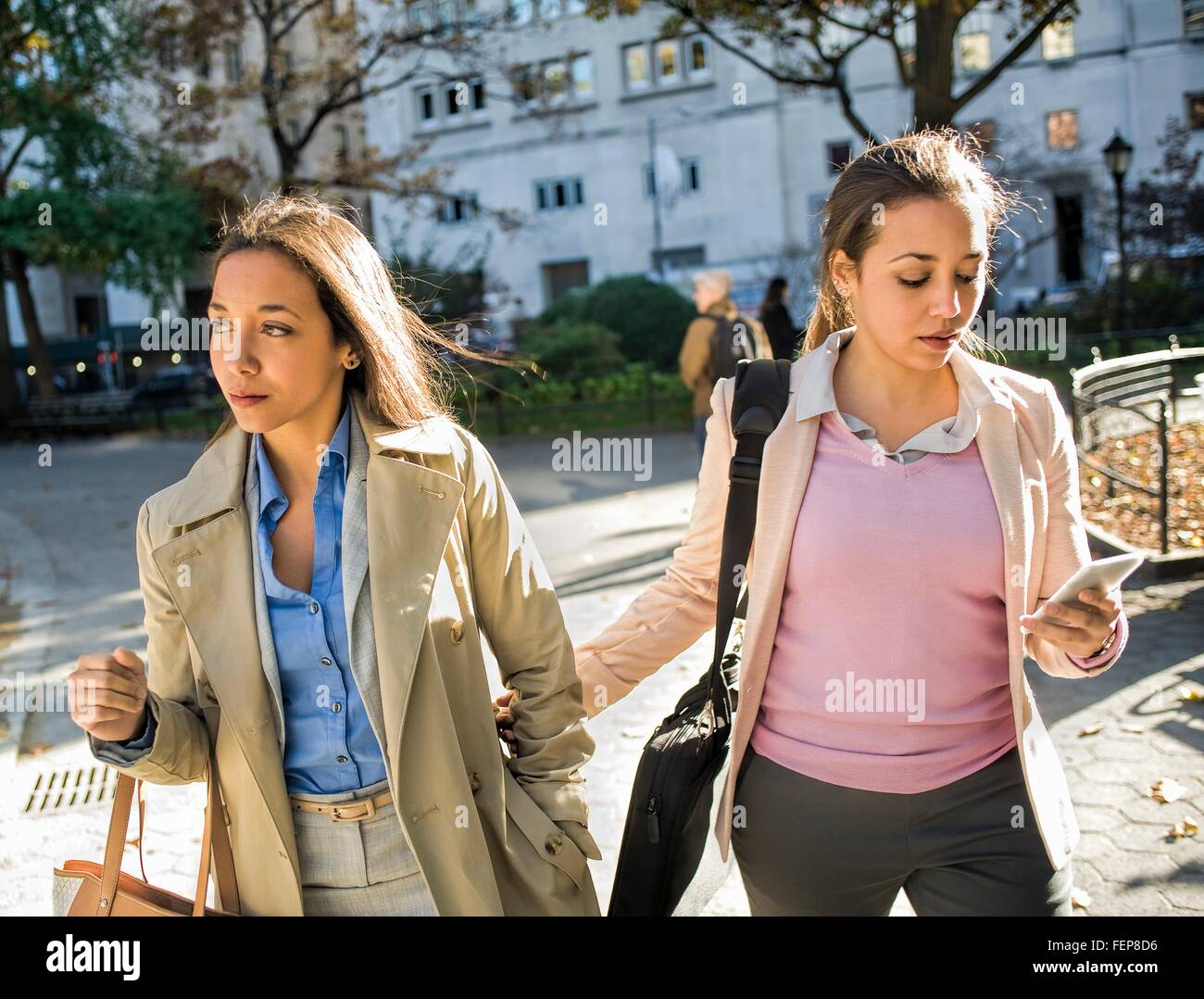 Young adult female twins walking arm in arm through city park Stock Photo