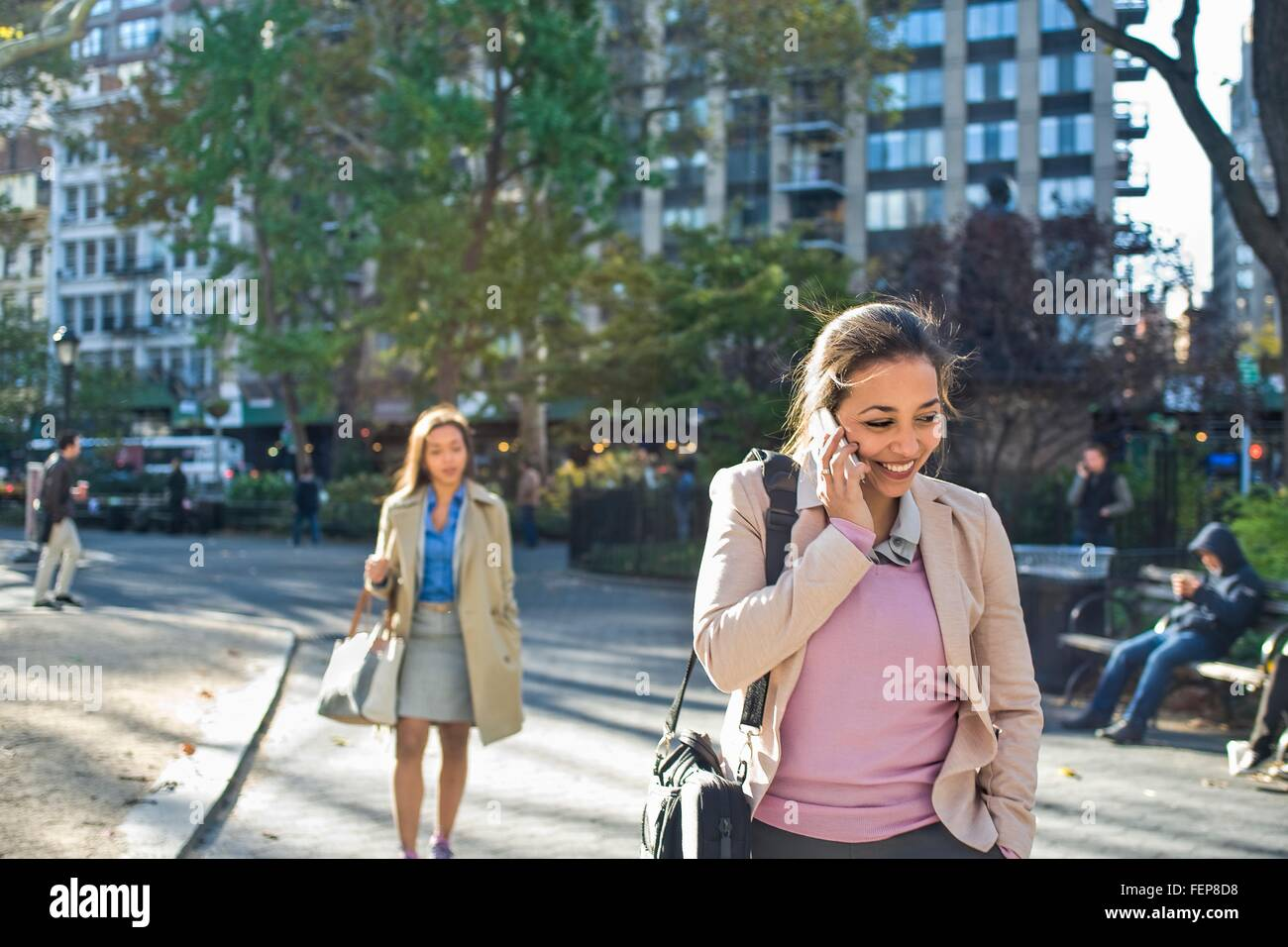 Young woman talking on smartphone whilst walking through city park - Stock Image