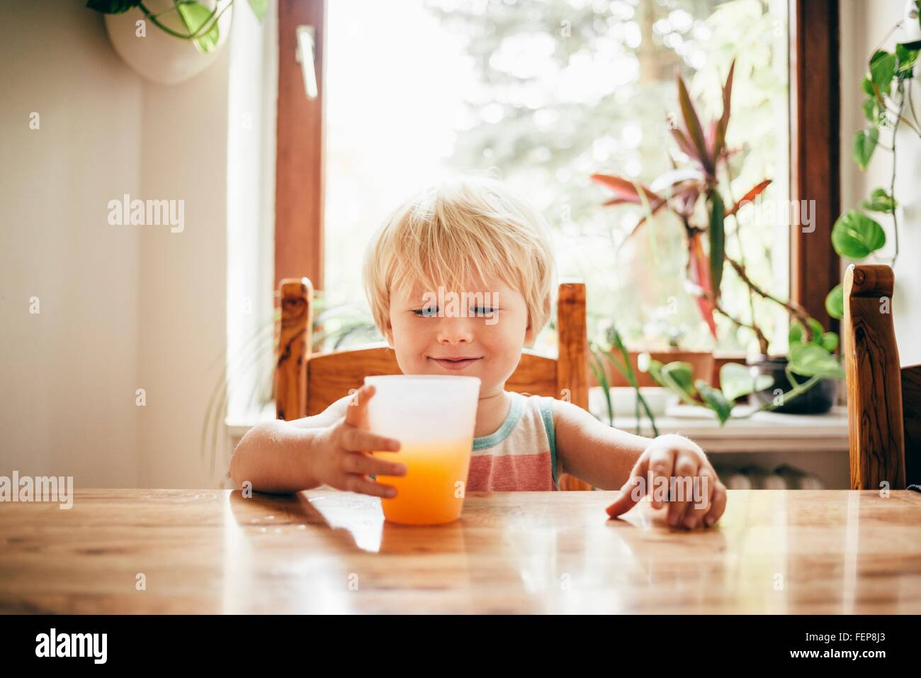 Boy sitting at table with beaker of orange juice looking down smiling - Stock Image